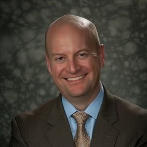 A bald white man in a brown suit with a light blue shirt and brown tie smiling in front of a gray background