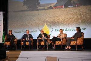 Three women and two men sitting in yellow chairs on a stage having a discussion with a large screen behind them showing a cornfield with the phrase Iowa Renewable Fuels Association on it