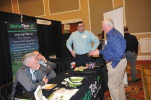 Two men in blue shirts standing and talking to two men in gray sweatshirts sitting at a black table with the words BetaTec in green and white on it in a hotel ballroom