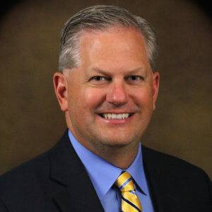 The CEO of NBB with gray hair smiling in front of a brown background while wearing a black suit with a blue shirt and blue and yellow tie